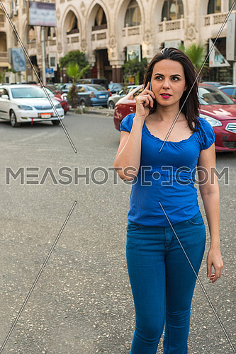 young lady talking in mobile phone in the street in korba area at day