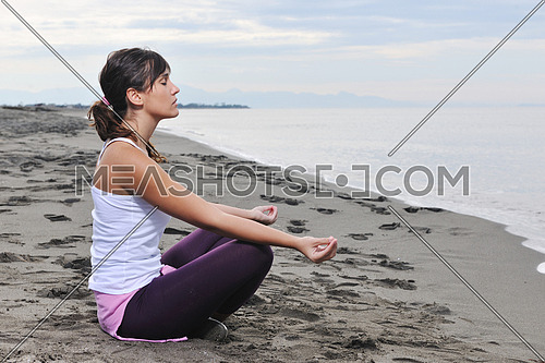 young woman meditating yoga in lotus positin on the beach at early morning