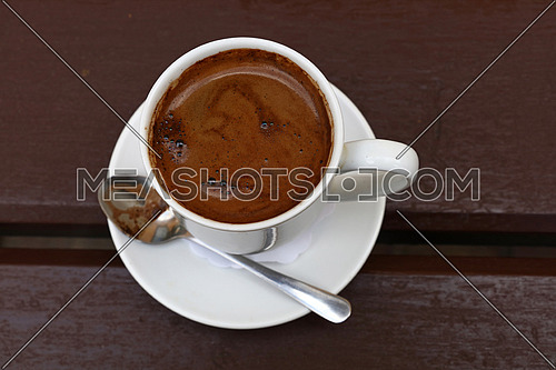 Turkish freshly brewed black natural ground coffee brown foam froth in full white cup with saucer and metal spoon over wooden table, detail close up, elevated top view