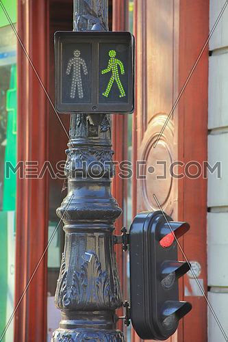 pedestrian Green signal on a rustic pole in an urban street