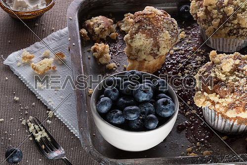 Muffins with crumbs and blueberry in a white bowl on a tray moist with jam and a fork aside