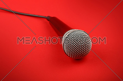 Black and silver wired vocal microphone with cable high angle view close up over red background, personal perspective