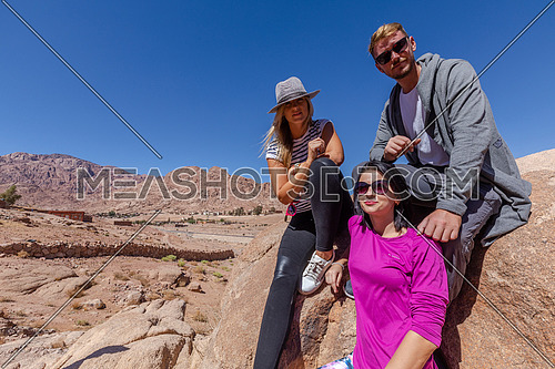 long shot group of tourists standing while exploring Sinai Mountain for wadi Freij at day.