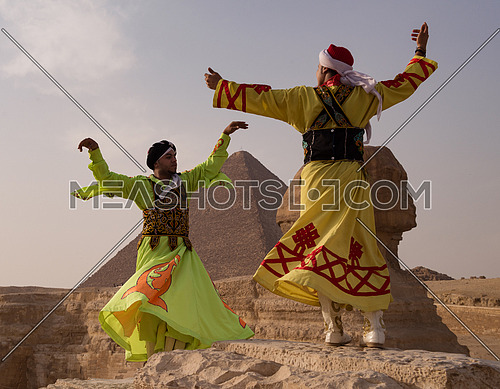 two Egyptian sufi dancers performing at the pyramids