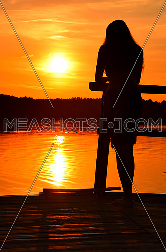 Sunset silhouette of one young woman with long hair standing on lake or river wooden pier and looking away, rear view