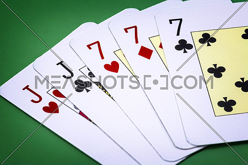 Poker hand call full house, composed by couple of j and three letters of the number seven on green background