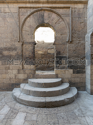 Wooden aged vaulted open door, three steps and stone wall, Medieval Cairo, Egypt