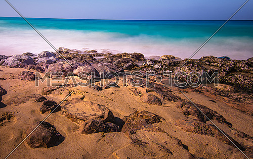 A rocky beach sand and sea long exposure