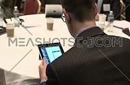 close shot from behind for a business man wearing suit and using his Tab in a conference.