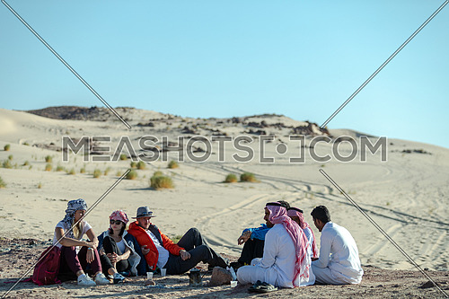 Group of tourists sitting with bedouin guides exploring Sinai Trail from Ain Hodouda by day.