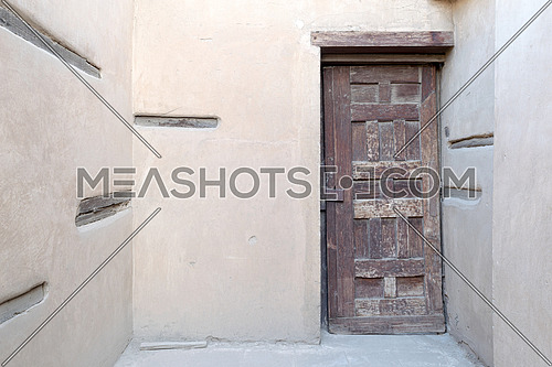 Wooden aged decorated door and stone wall, Medieval Cairo, Egypt