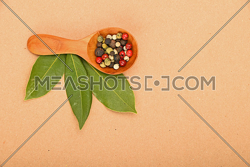 Three green bay laurel leaves and mix of peppercorn in wooden scoop on brown kraft paper background