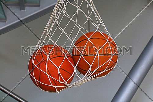Close up two basketball balls hanging in mesh sack, low angle side view