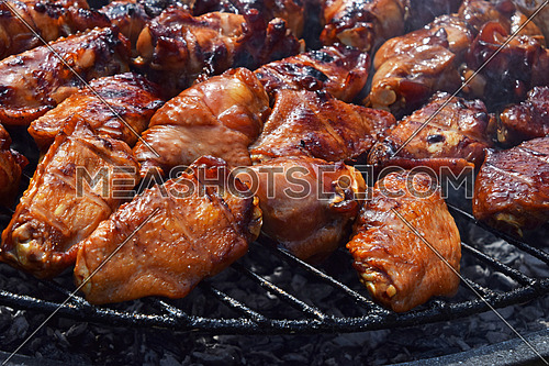 Chicken buffalo or teriyaki sauce wings cooked grilled on bbq smoke round grill, close up