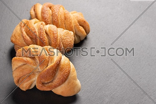 sweet, homemade brioche with cinnamon on dark background with copy space