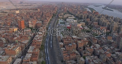 Aerial shot for the city beside the River Nile while Metro Passing by in Cairo at sunset