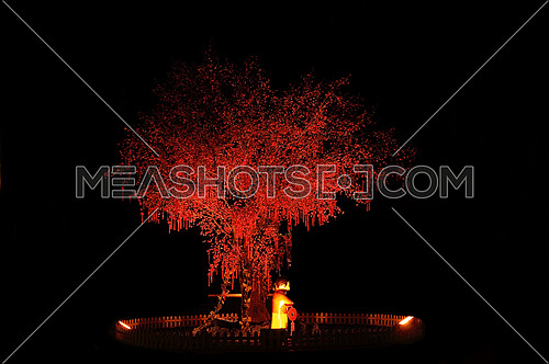 red chinese new year tree with small statue illuminated with red light