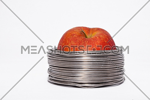 Wired apple: whole red apple in coils of aluminum wire isolated on white background