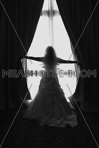 a Bride in silhouette wearing a wedding dress near a window and opening curtains