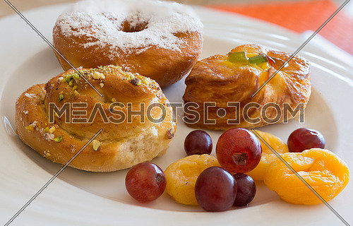 Danish pastry and  fruits on white dish,close-up.