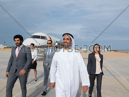 young successful businessmen walking with their Arab business partner in front of private airplane