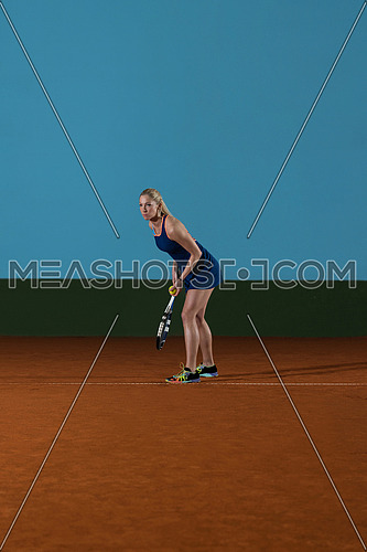 Portrait Of Female Tennis Player With Racket Ready To Serves Toss Ball