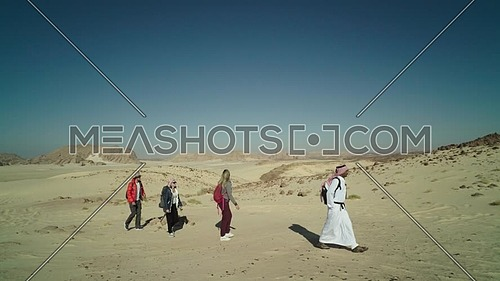 Follow shot for group of tourists walking on sands with bedouin guide while exploring Sinai Trail from Ain Hodouda at day.