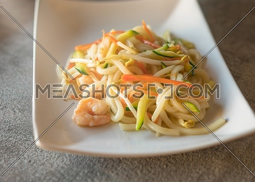 Yaki udon served on rectangular white plate on dark gray stone background