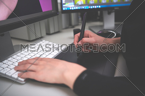 Female hands using keyboard and graphic tablet close up. Graphic designer at the job. Freelancer editing photos.