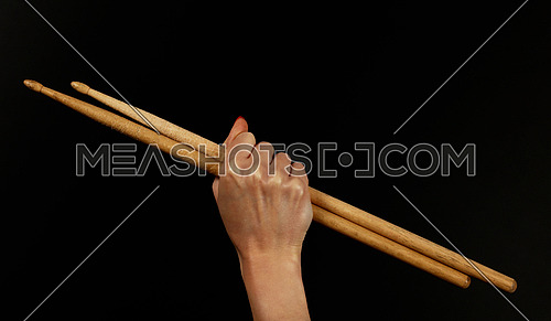 Close up woman hand with red nails holding two drumsticks over black background, side view