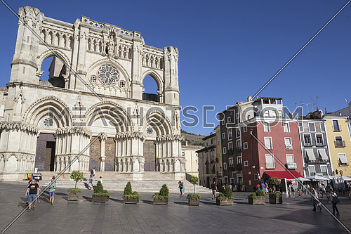 CUENCA, SPAIN - APRIL 2, 2016: Tourists walk near the facade of the Cuenca's Cathedral, The cathedral is dedicated to St Julian, gothic english-norman style, XII century, called the Basilica of Our Lady of Grace
