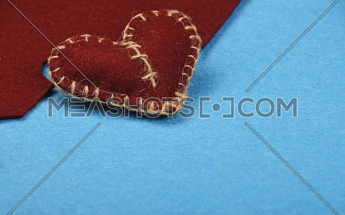 Felt craft and art, one handmade brown stitched toy heart with cut out on blue felt background, top view