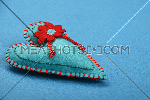 Felt craft and art, one handmade teal stitched toy heart with red flower on blue background, low angle view