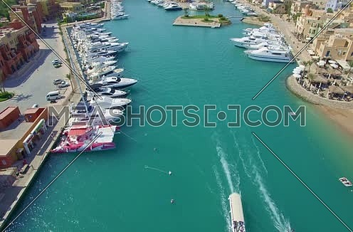 Drone shot flying above Al Gouna Marina with moving boats at Day