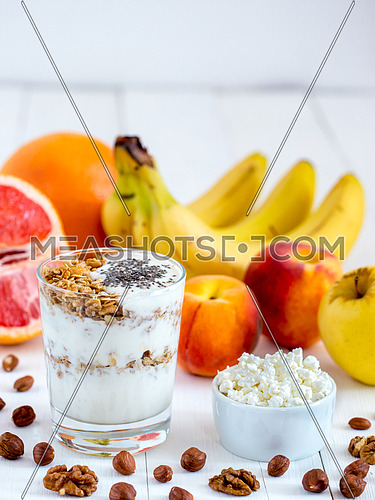 Healthy breakfast: cottage cheese with yogurt, fruits and nuts on white wooden background. Dieting, healthy lifestyle concept meal. Vertical with copyspace