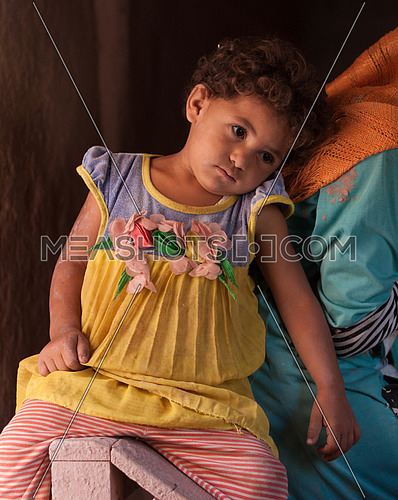 Little girl attached to her elder sister who works at the pottery school in Fayoum, Egypt