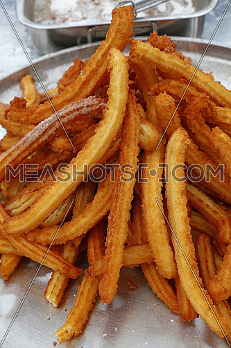 Heap of sweet fresh churros, traditional Spanish or Portuguese deep fried dough pastry snack cooked close up, high angle view