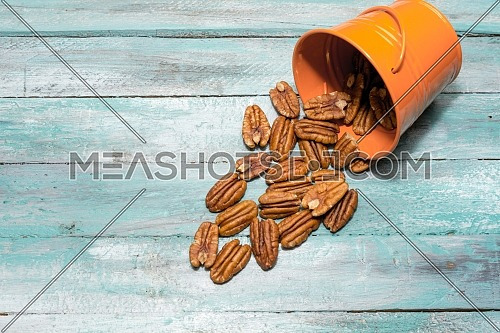 Close-up of Pecans spilling out of a container. Healthy food