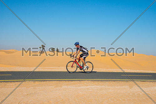 a cyclist cycling on a track in the desert in al qudra cycling track Dubai 6 February 2016