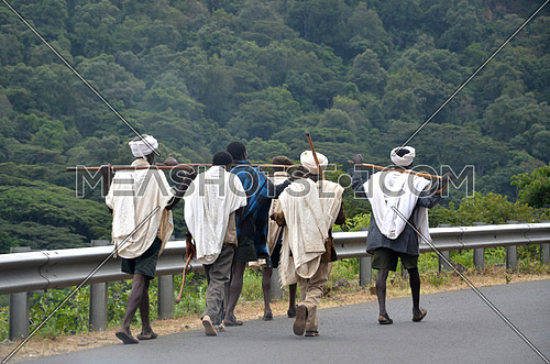six working class men walking in the street by a cliff