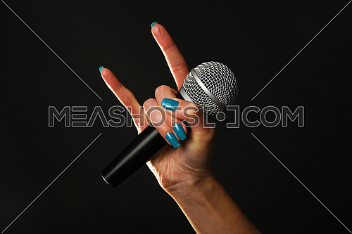 Woman hand with blue nails holding microphone with devil horns rock metal sign isolated on black background