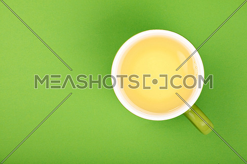 One full freshly brewed clear green oolong tea in big cup with saucer on green paper background, top view, bird eye view