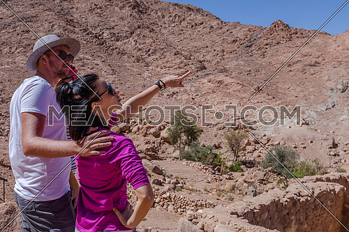 Group of tourists from behind exploring Sinai Mountain for wadi Freij at day.