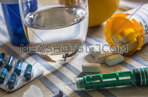 capsules next to a glass of water and Insulin injector, conceptual image
