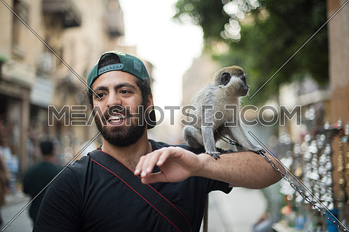 Portrait of a young middle eastern tourists who enjoy with a monkey on his shoulder