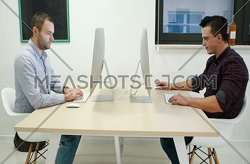 Mid-shot for two young people sitting opposite each other in an office and working on computers.