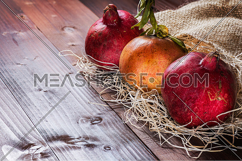 Pictured three pomegranates placed on straw and jute sack on wooden background