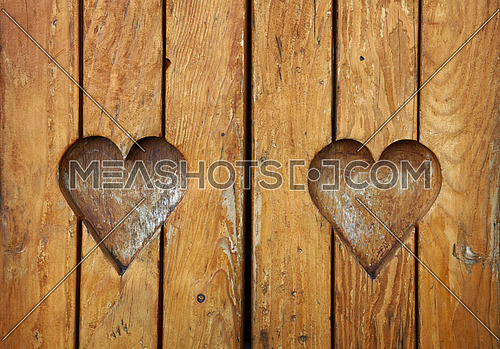Two heart shaped elements, symbol of love, romance and togetherness, wood carved cut in vintage old grunge natural brown wooden planks texture background, close up