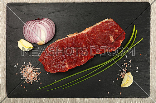 One raw beefsteak red meat cut, spices, peppercorn in wooden scoop, green spring chive, onion, garlic and Himalayan salt on black slate board, close up, elevated top view, directly above