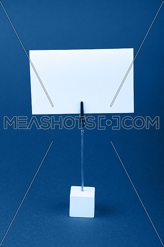 Blank white cardboard sign with copy space on classic metal note holder over dark blue paper background, front side view